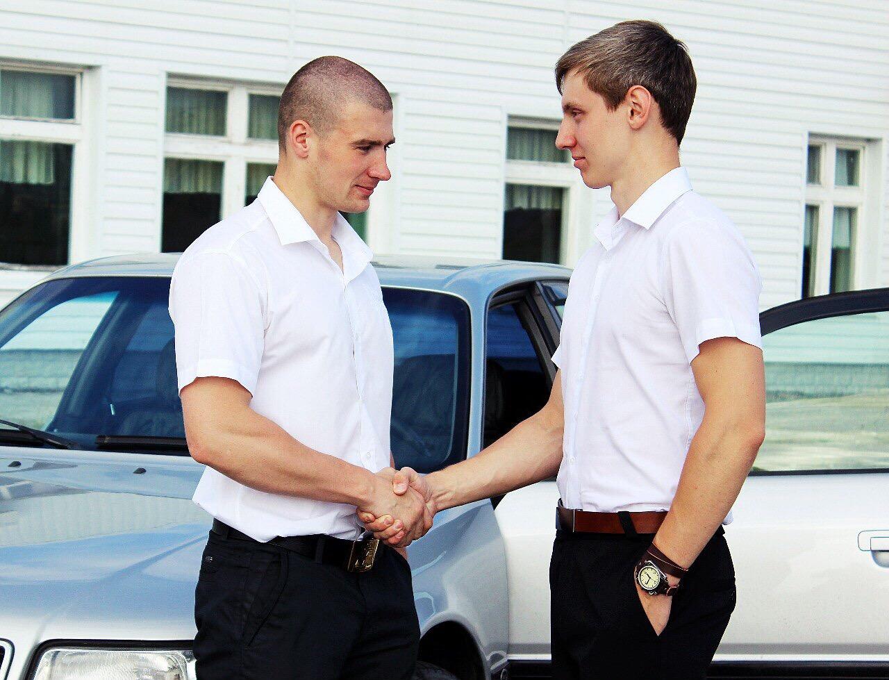 deux hommes se serrent la main devant voiture